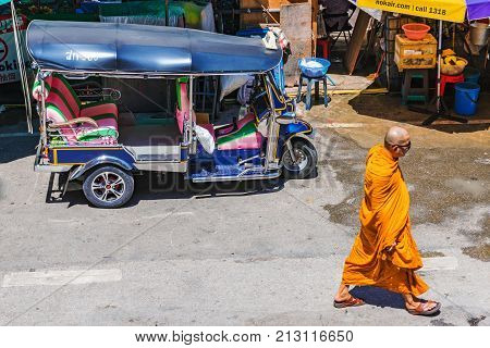 CHIANG MAI THAILAND - JULY 27: Street scene of a tuk tuk and a monk walking in the downtown area of Chiang mai on July 27 2017 in Chiang Mai