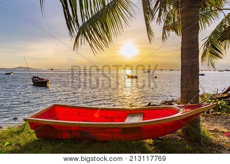 Sunset sea view with boats and palm trees in Siracha Thailand