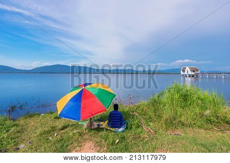 CHONBURI THAILAND - AUGUST 10: This is Bang Phra reservoir with a fisherman sitting by the lake. Bang Phra is a popular fishing spot amongst locals on August 10 2017 in Chonburi