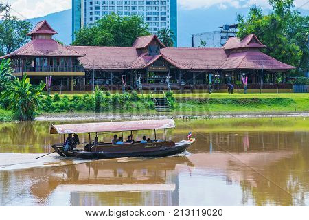 CHIANG MAI THAILAND - JULY 29: This is a view of a tourboat and riverside buildings along the famous Ping river on July 29 2017 in Chiang Mai