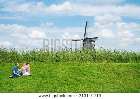 ROTTERDAM, HOLLAND -AUGUST 22, 2017; Young couple with baby sitting on grassy dyke with windmill behind in Kinderdijk district popular tourist destination with it's scenic fields, ponds, dykes and old windmills.