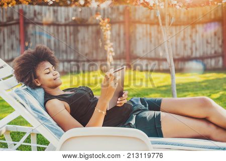Attractive young Brazilian lady laying on lounge and chatting with friend via tablet pc; calm black teenage female is chilling on chaise-longue in park and watching music videos with digital pad
