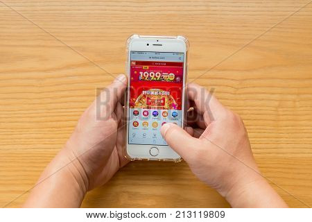 ZhongshanChina-November 112017:man shopping through mobile on Taobao on Chinese online shopping day on November 11.Nov 11 is the shopping day of China and online shopping is very popular in China.