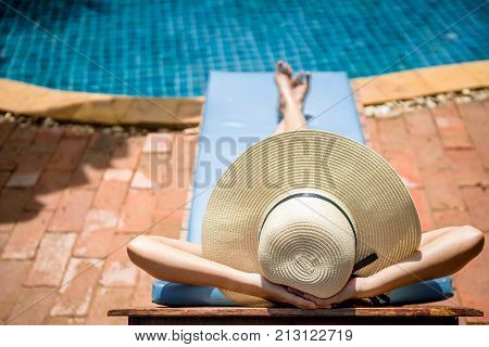 Women wearing bikini or swimware suits at swimming pool relax on the pool bed at the resort of Pattaya in Thailand.
