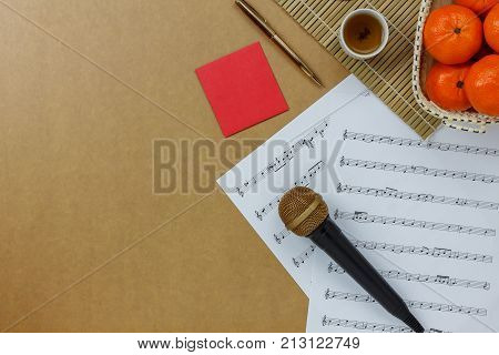 Table top view of music sheet note and accessories Chinese new year & Lunar festival concept.Essential items on modern rustic brown wooden at home office desk.Orange in basket with tea and red pocket.