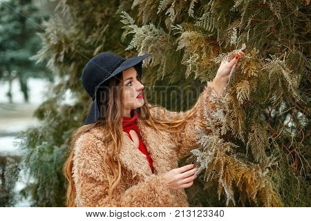Young attractive girl outdoors in winter. She is wearing a wide-brimmed hat and a fur coat. The girl is standing next to the fir-tree. She considers the hoarfrost on the tree