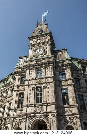 Classic clocktower building in Quebec City Canada with flag of quebec on a sunny day blue sky