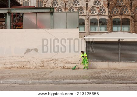 Barcelona Spain-May 27 2013 Female council worker sweeping the streets in front of the Sagrada Familia Cathedral Barcelona Spain