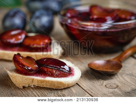 Fresh homemade plum jam in a glass bowl on a rustic table. Plum jam with a spoon made of dark wood and ripe plums.