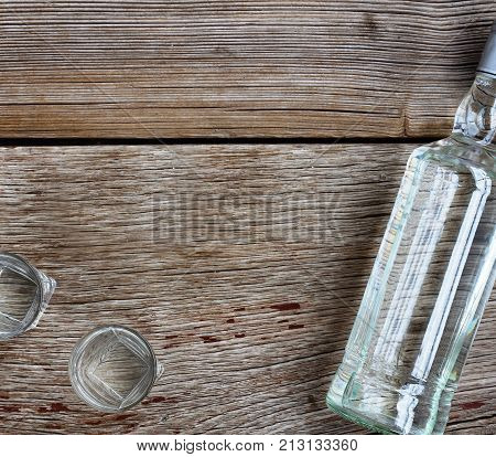 Vodka Luxury. Vodka Bottle With Shot Glasses On The Board. On Wooden Background.