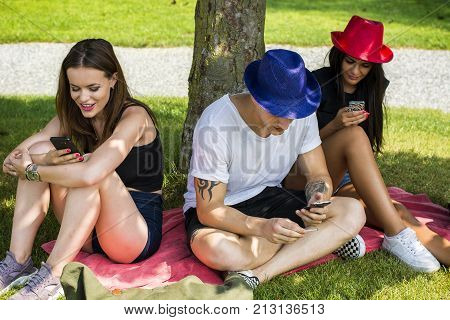 Group of young people sitting under tree, using their smartphones and communicating with each other or absorbed with them. Concepts of lack of communication, self-absorbtion, overuse of technology