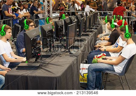 ROME, ITALY. October 03, 2015: Boys tournament players and gaming consoles. Row of young boys playing with a console. Wearing headphones. Romics 2015 in Rome, Italy. Festival of comics and gaming.