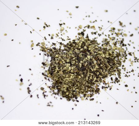 Spilled ground pepper on the white background