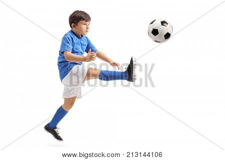 Little soccer player kicking a football in mid-air isolated on white background