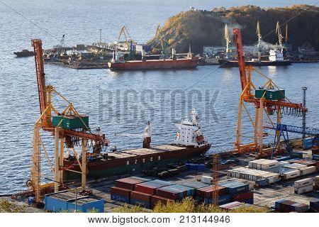 PETROPAVLOVSK-KAMCHATSKY CITY KAMCHATKA PENINSULA RUSSIAN FAR EAST - OCTOBER 3 2017: View on ships at pier and port cranes on commercial seaport Petropavlovsk-Kamchatsky on shore of Avacha Bay.