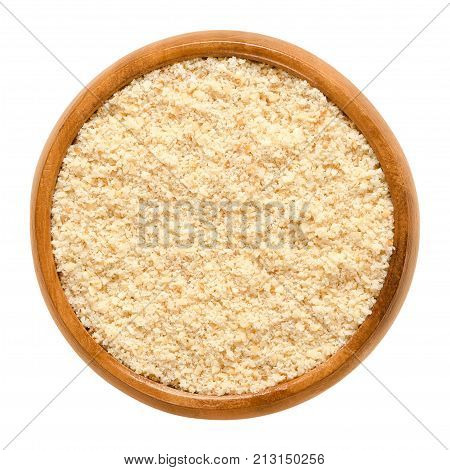 Ground hazelnuts in wooden bowl. Meal of the nut of the hazel, Corylus avellana, also known as cobnut or filbert nut. Grounded seeds. Isolated macro food photo close up from above on white background.