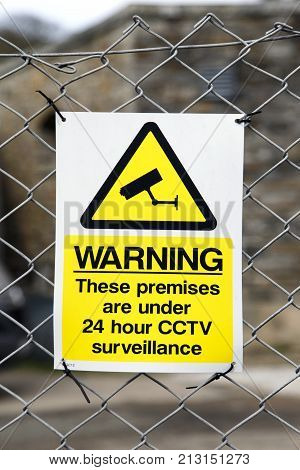 Warning Sign with 24 hour CCTV Surveillance attached to a perimeter fence