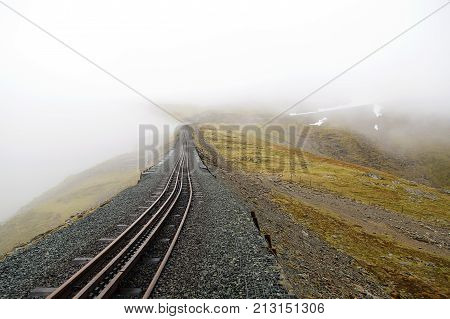 The Snowdon Mountain Railway is a narrow gauge rack and pinion mountain railway in Gwynedd. It is a tourist railway that travels for 4.7 miles from Llanberis to the summit. Mist covers the mountain
