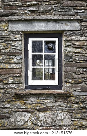 Close up of a window pane on a 15th century building with rustic stone walls in a vertical format