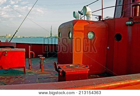 An old red lightship which has served the seas for over a century rests in its harbour in the afternoon sun. It sharply shows hinges, nuts , bolts, steel plates, welded repairs, rust and the infuence of time. The background is 'romantically' blurred but s