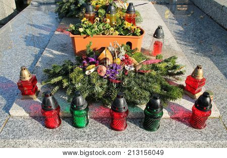 grave decorated with many lanterns and arranged branches of spruce tree