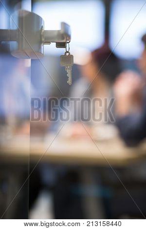 Open  glass door with keys, key in keyhole