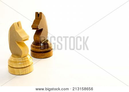 The white and the black chess knight of wood on the white background