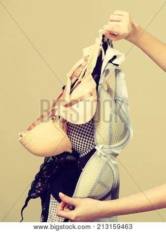 Bosom concept. Female holding many bras in hand choosing witch bra to wear