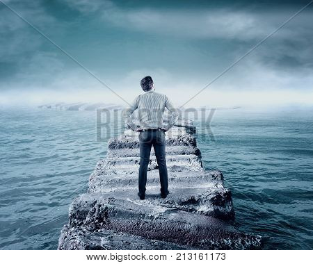 Businessman standing on pontoon of rocks in the sea. Bifurcation of rocks to the sea. Choosing the right path concept.