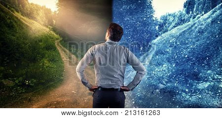 Man standing in front of two different roads one road warm climate and one road cold climate. The concept of changing seasons.
