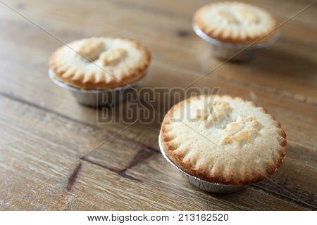 Close Up Shot Of Three Mince Pies In Foil Cases, Traditional Christmas Dessert