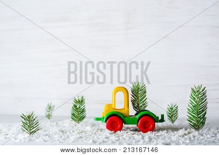 A Small Toy Car Is A Crane. New Year And Christmas Background. Mini Christmas Trees From Real Spruce