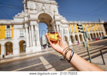 Holding portuguese egg tart pastry called pastel de Nata outdoors on the triumphal arch background in Lisbon
