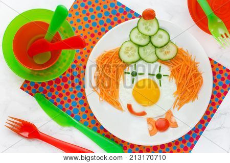 Dinner or breakfast for kids - fried egg with vegetables in the shape of clown face. Creative food art idea for children meal top view