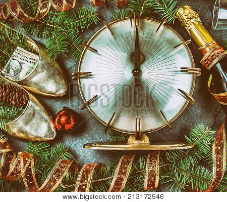 NEW YEAR CELEBRATION. Traditional put money to shoe for have money en New Year. Flat lay composition with vintage clock, shoes with dollars, champagne, Christmas decorations.