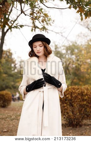 Retro gangster girl in black hat and fur coat in autumn park against a background of yellow trees looking down. Retro. On open air.