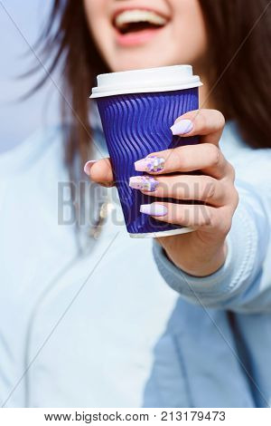 Happy girl holds paper eco mug in her hand with coffee milk or tea. Drink to take out. Take-away drink. Hand with beautiful manicure holds blue glass girl with beautiful smile in blue jacket