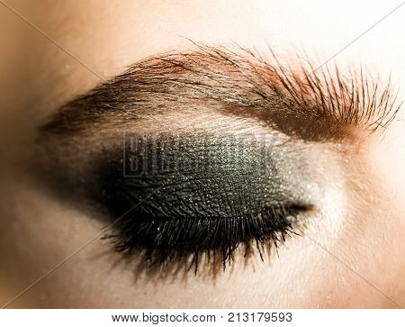 Eye shadow eye makeup black shadows on the female eyes. Mascara eyebrows and eyes with makeup. Beautiful female eye close up