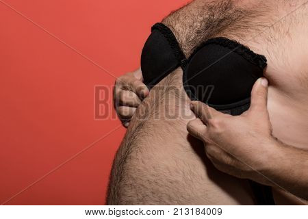 fat man in female bra. male hairy belly with lingerie. gay and lgbt. transgender and bisexuality. naked guy try on female brassiere copy space