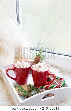 Red cup of hot chocolate with marshmallow on windowsill. Weekend concept. Home style. Christmas time morning. poster