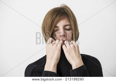 sad attractive woman is pulling up pullover collar. Lifestyle concept. Isolated studio shot.