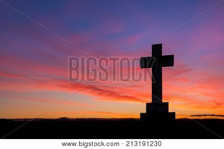 Stone cross on a hill area with a wonderful dawn morning sky.