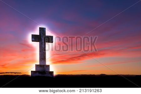 Stone cross with a glow around it on a hill area with a wonderful dawn morning sky.