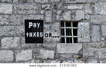 The concept of the consequences of tax evasion. The inscription on the prison wall: pay taxes or ...