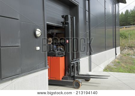 Picture of a industrial building. Male worker driving out of a warehouse on the fork-lift-truck