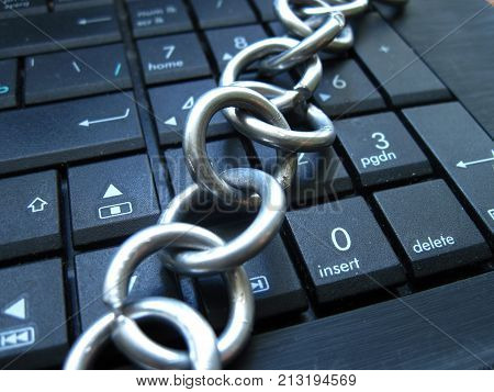 Chain on computer keyboard. It means laptop banned or internet banned. Block chain sign to mine cryptocurrency. Symbol of computer addiction, games, social networks and so on
