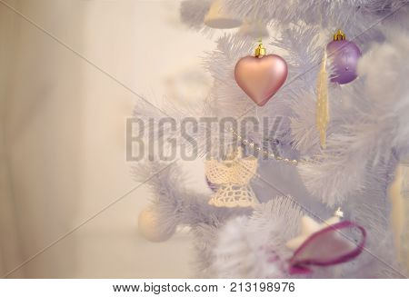 Soft pastel christmas tree decoration on a faux christmas fur-tree. Decorated christmas tree with old fashioned christmas-tree decorations. Merry Christmas and Happy New Year. Christmas time.