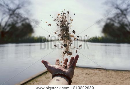 nature mood background. human hand throwing river rocks in air