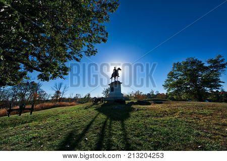Sun setting behind a Gettysburg Battlefield Memorial Statue in Autumn