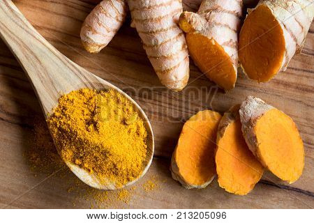 Turmeric powder on a wooden spoon with fresh turmeric root in the background